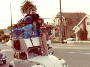 Frances and Tim on VW Beetle loaded silly tall in Alameda, CA, 1984